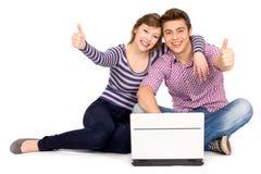 Pares com os polegares que usam acima o portátil Imagem de Stock