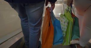 Pares com os sacos de compras que montam a escada rolante filme