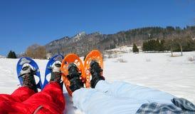 Pares com os sapatos de neve azuis e alaranjados nas montanhas Foto de Stock