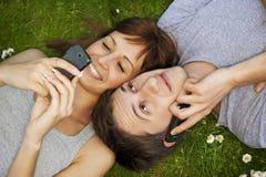 Pares com os telefones móveis ao ar livre Fotografia de Stock