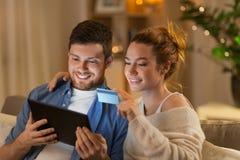 Pares com PC da tabuleta e cartão de crédito em casa fotos de stock royalty free