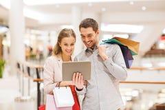 Pares com PC e sacos de compras da tabuleta na alameda Fotografia de Stock Royalty Free