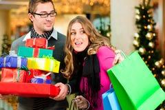 Pares com presentes de Natal e sacos na alameda Fotos de Stock