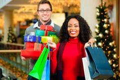 Pares com presentes de Natal e sacos na alameda Imagens de Stock Royalty Free
