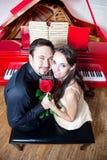 Pares com a rosa perto do piano vermelho imagem de stock