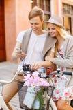 Pares com smartphone e bicicletas na cidade Imagens de Stock Royalty Free