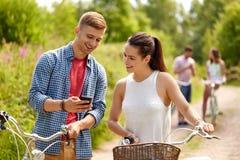 Pares com smartphone e bicicletas no verão imagens de stock royalty free