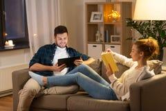 Pares com tablet pc e livro em casa foto de stock royalty free