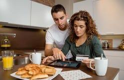 Pares com a tabuleta eletrônica que revê o crédito Foto de Stock