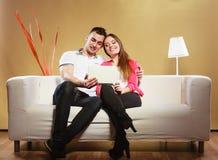 Pares com a tabuleta que senta-se no sofá em casa Imagem de Stock Royalty Free