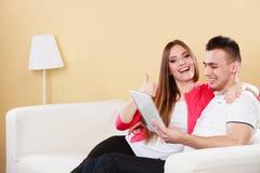 Pares com a tabuleta que senta-se no sofá em casa Foto de Stock