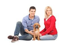 Pares com um filhote de cachorro do corso do bastão Fotos de Stock Royalty Free
