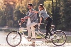 Pares com uma bicicleta em tandem fotografia de stock