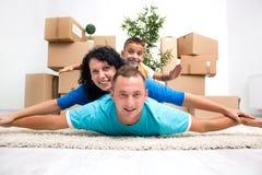 Pares com uma criança em sua casa nova que coloca no assoalho com carro foto de stock royalty free