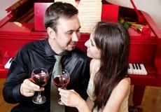 Pares com vidros do vinho perto do piano Fotografia de Stock Royalty Free