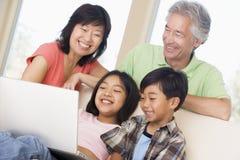 Pares con dos niños en sitio con la computadora portátil Fotografía de archivo
