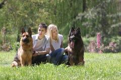 Pares con dos perros en fondo natural Imágenes de archivo libres de regalías