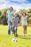 Pares con el adolescente que juega con el balón de fútbol Imagen de archivo