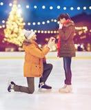Pares con el anillo de compromiso en la pista de patinaje de Navidad Foto de archivo
