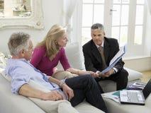 Pares con el consejero financiero en el sofá Imágenes de archivo libres de regalías