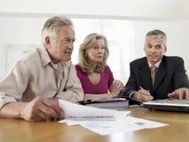 Pares con el consejero financiero en la tabla Foto de archivo libre de regalías
