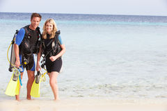 Pares con el equipo del buceo con escafandra que disfruta de día de fiesta de la playa Imagen de archivo libre de regalías