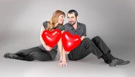 Pares con el globo del corazón que se sienta en estudio Imagenes de archivo
