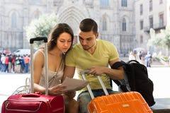 Pares con el mapa de la lectura del equipaje Imagen de archivo libre de regalías