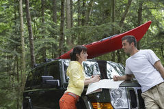 Pares con el mapa en capo del coche en bosque foto de archivo