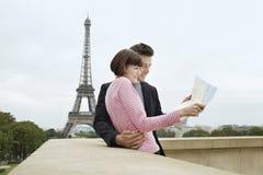 Pares con el mapa en Front Of Eiffel Tower Foto de archivo libre de regalías