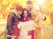 Pares con el mapa turístico en parque del otoño Imágenes de archivo libres de regalías