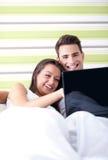 Pares con el ordenador portátil en cama imágenes de archivo libres de regalías