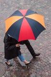 pares con el paraguas en lugar de los adoquines en la ciudad Fotos de archivo