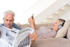 Pares con el periódico y el teléfono móvil en sala de estar fotografía de archivo libre de regalías