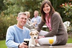 Pares con el perro de animal doméstico al aire libre que disfruta de la bebida en Pub imagen de archivo