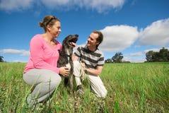 Pares con el perro en campo foto de archivo libre de regalías