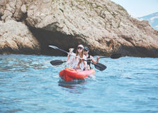 Pares con el perro que camina en canoa del mar Fotos de archivo