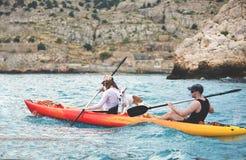 Pares con el perro que camina en canoa del mar Fotografía de archivo