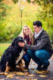 Pares con el perro que disfruta de otoño en naturaleza Imagenes de archivo