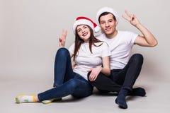 Pares con el signo de la paz y los sombreros de la Navidad Fotos de archivo libres de regalías