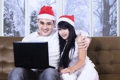 Pares con el sombrero y el ordenador portátil de santa en el sofá Fotos de archivo libres de regalías