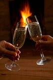 Pares con el vidrio de Champagne Relaxing By Fire Fotos de archivo