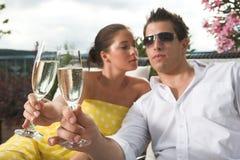 Pares con estilo que tienen una bebida en terraza Fotos de archivo