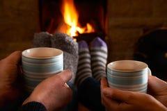 Pares con la bebida caliente que se relaja por el fuego Fotos de archivo libres de regalías