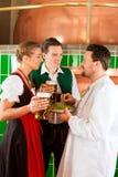 Pares con la cerveza y su cervecero en cervecería Foto de archivo libre de regalías
