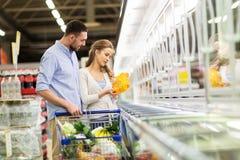 Pares con la comida de compra del carro de la compra en el ultramarinos imagen de archivo