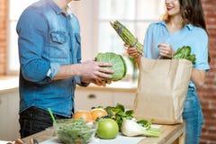 Pares con la comida sana en la cocina imagenes de archivo