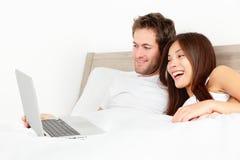 Pares con la computadora portátil en cama Imágenes de archivo libres de regalías