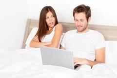 Pares con la computadora portátil en cama Imagen de archivo libre de regalías