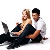Pares con la computadora portátil, sentándose en suelo Imagenes de archivo
